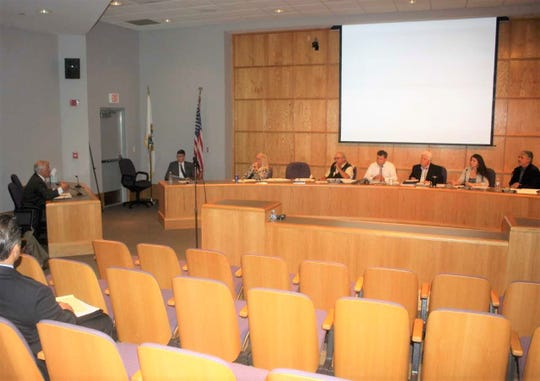 Paul Zelenak (left) answers questions from South Lyon city council members.