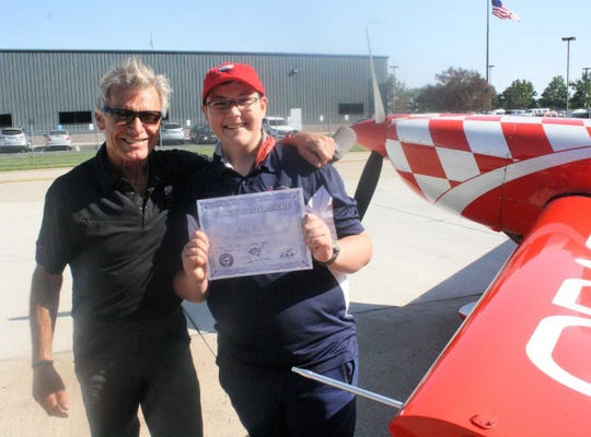 Buster Wurm holds up his Young Eagle certificate that was presented to him by Sean Tucker (left)