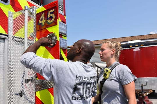 Holley-Navarre Fire District Engineer Earner Harris, left, and firefighter Kailey White look over one of the district's two new engines at Station 45 on Friday.