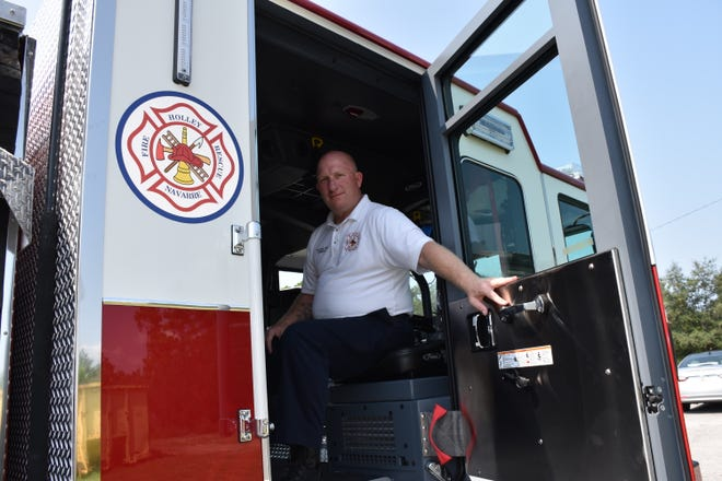 Holley-Navarre Fire District Battalion Chief Howie Rounsaville at Station 45 holds open the door of one of the district's two new engines that arrived on Wednesday, Aug. 22, 2018.  The other engine will be housed at Station 41 and the engines replace two others that were about 20 years old.