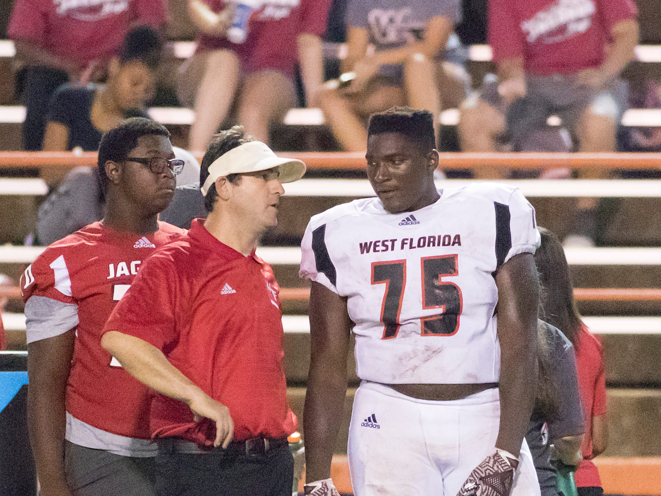 Jaguars head coach Rhett Summerford talks with Darius Washington (75) during the West Florida vs Escambia football game at Escambia High School in Pensacola on Thursday, August 23, 2018.