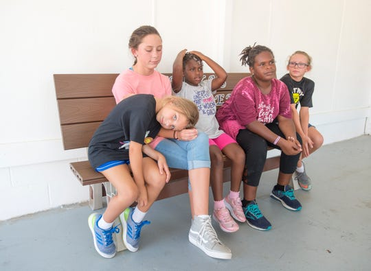 Spencer Scapin, 6, from left, Sydney Scapin, 12, Emmy Bellas, 7, Addy Bellas, 10, and Ava Scapin, 10, sit on Dericka's buddy bench at St. John the Evangelist Catholic School in Pensacola on Friday, Aug. 24, 2018. The bench was created in the memory of 9-year-old Dericka Lindsay, who died when she was sat on as punishment at home.