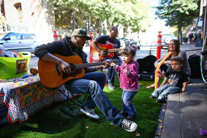 A musician plays the guitar at a pop-up park in Seattle.