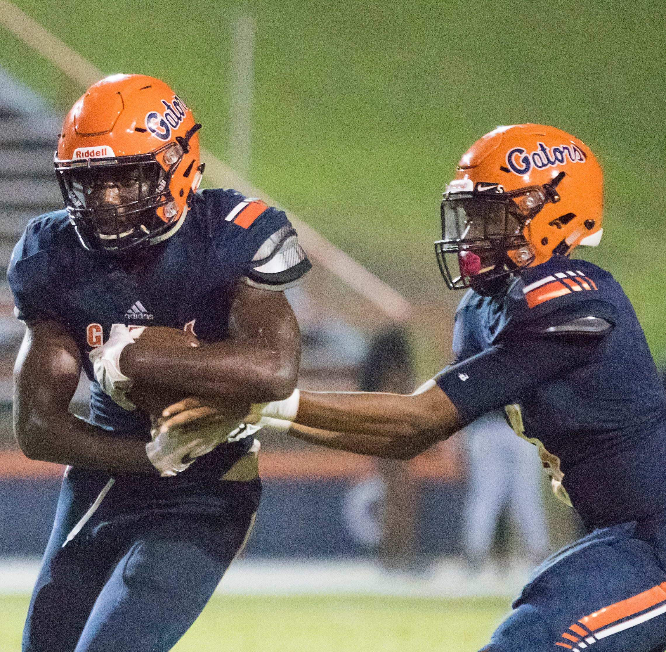 Gator quarterback (5) hands off to Frank Peasant (1) during the West Florida vs Escambia football game at Escambia High School in Pensacola on Thursday, August 23, 2018.