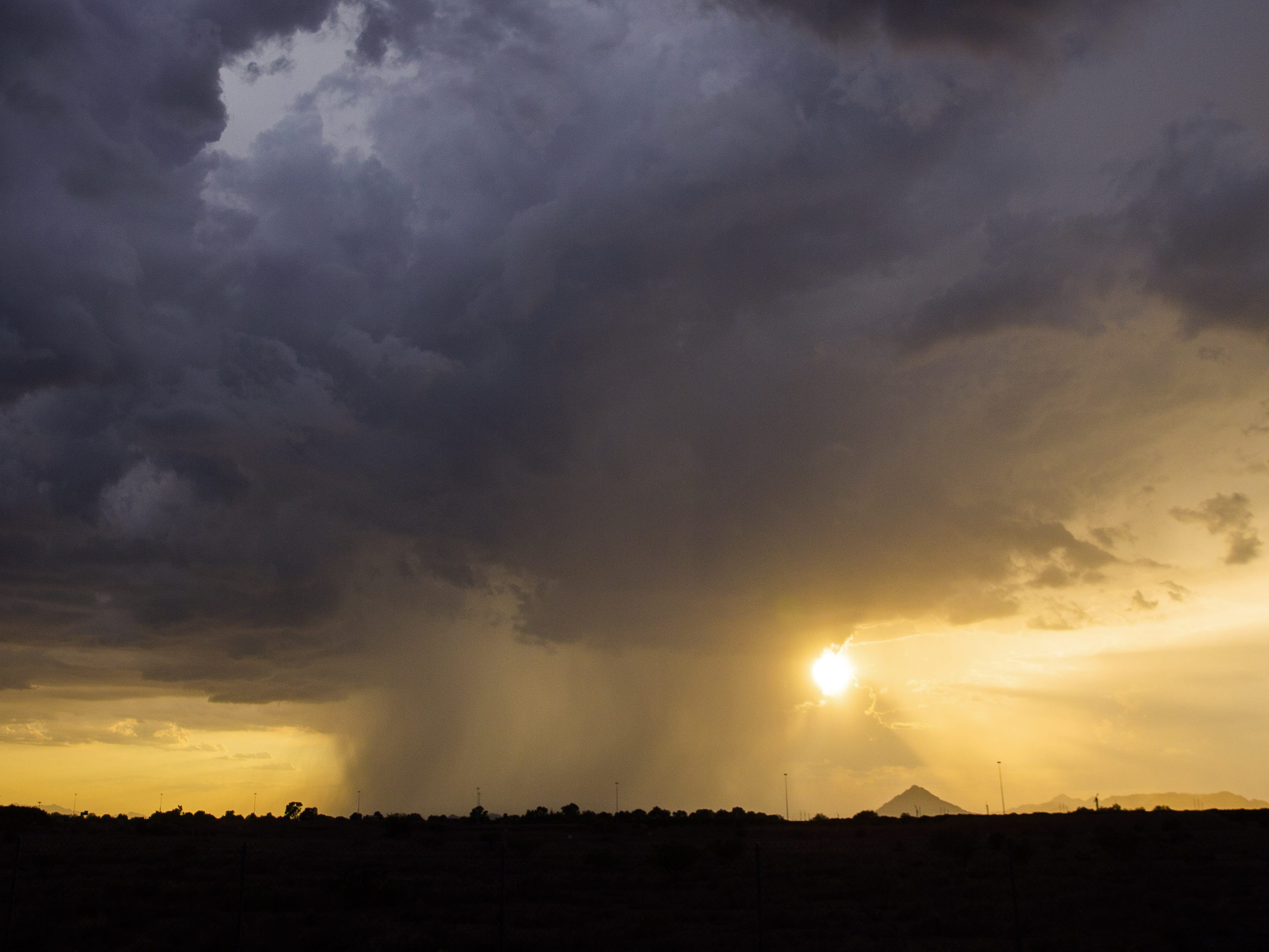 The sun sets behind Camelback Mountain and a monsoon storm, dropping rain over Phoenix on Aug. 23, 2018.