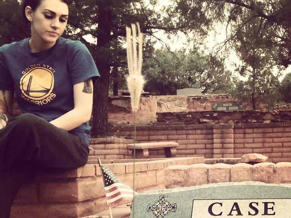 Stefani Case sitting next to Kalin Case's headstone.