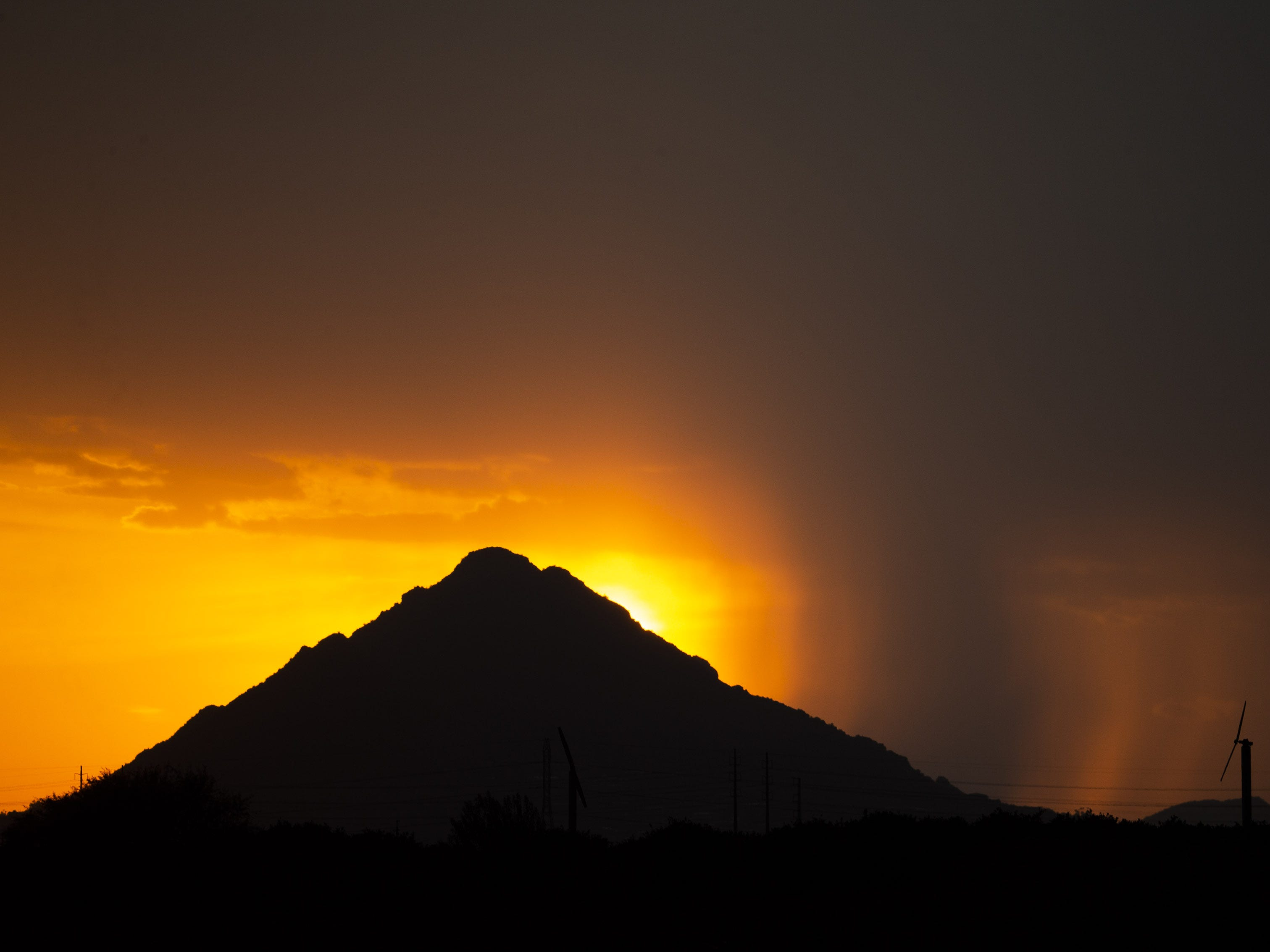 A monsoon storm drops rain behind Camelback Mountain in Phoenix on Aug. 23, 2018.
