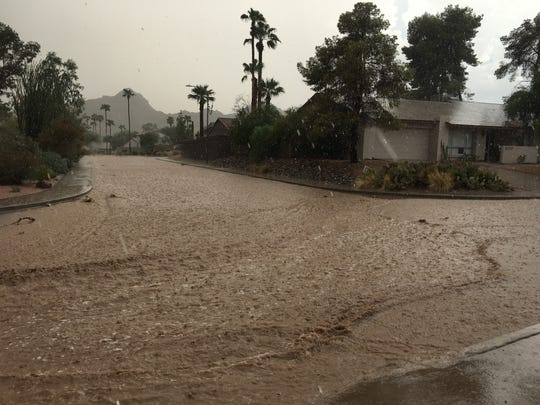 Streets flood near 24th Street and Shea Boulevard in Phoenix during a monsoon storm.