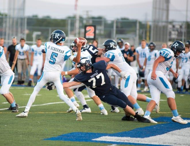 Marysville's Parker Foster (77) reaches for Richmond High School quarterback Brandon Schorman before he throws a pass Thursday, Aug. 23, 2018, during their game at Marysville High School.