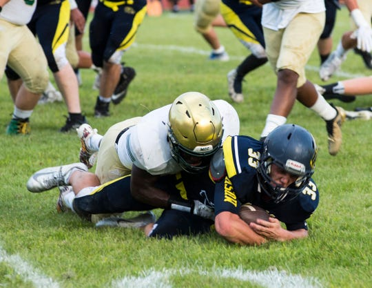 Algonac High School's Jack Jewell (33) is tackled by Muskegon Catholic Central's Solomon Waller during their game Friday, Aug. 24, 2018.