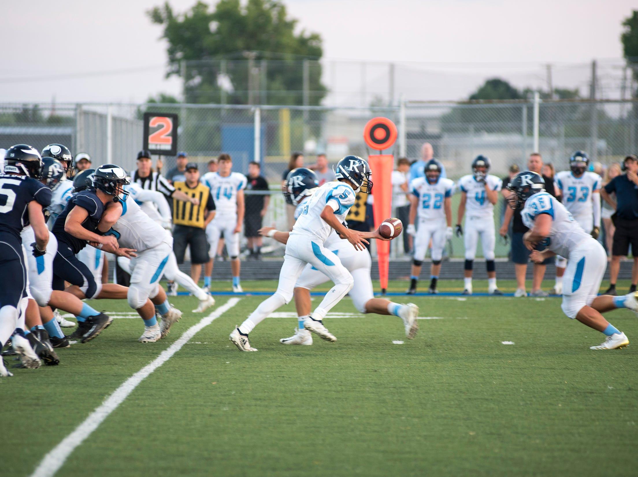 Richmond High School quarterback Brandon Schorman (5) hands off the ball to running back Noah Montanari during their game against Marysville Thursday, Aug. 23, 2018, at Marysville High School.