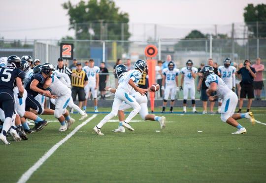 Richmond High School quarterback Brandon Schorman (5) hands off the ball to runningback Noah Montanari during their game against Marysville Thursday, Aug. 23, 2018, at Marysville High School.