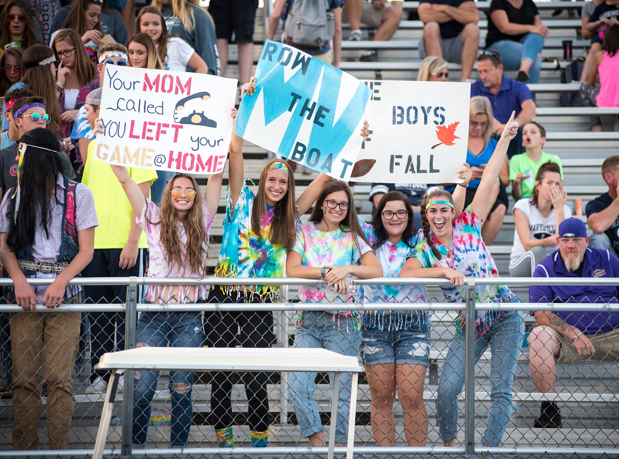 Marysville students hold up signs and cheer during halftime of the Vikings' game against Richmond High School Thursday, Aug. 23, 2018, at Marysville High School.