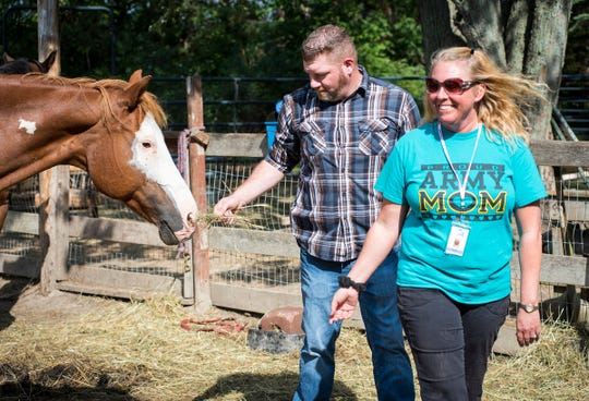 Adam Trupe, left, and Region 10 veterans coordinator Christy Koons bribe Lucky, a 17-year-old horse to follow them during a game Friday, Aug. 24, 2018, at Wisdom Ranch in Emmett. Wisdom Counseling LLC hosts an equestrian therapy session for veterans on the farm.