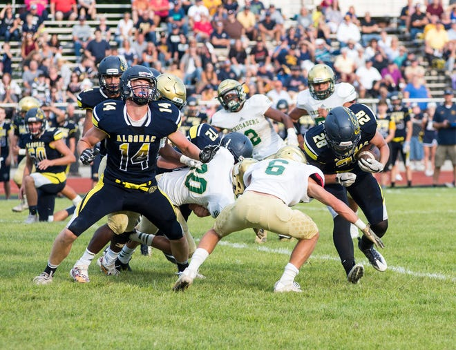 Algonac High School's EJ Peterson (28) is grabbed by Muskegon Catholic Central's Carson St. Amour during the second quarter of their game Friday, Aug. 24, 2018, at Algonac High School.