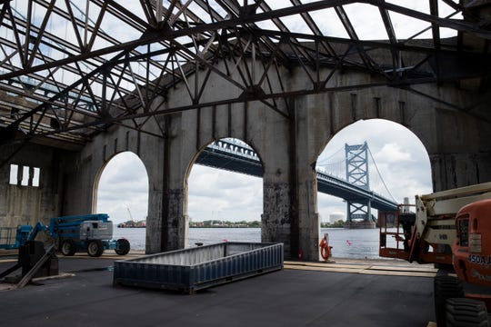 The Benjamin Franklin Bridge is framed by Pier 9 and future home of the Cherry Street Pier now under construction in Philadelphia, Wednesday, Aug. 22, 2018. The planned development is expected to include an open-air park, cafe, a bar and a series of artists' studios and offices. The more than 55,000 square foot space will also have areas designed for retail markets and food vendors. (AP Photo/Matt Rourke)