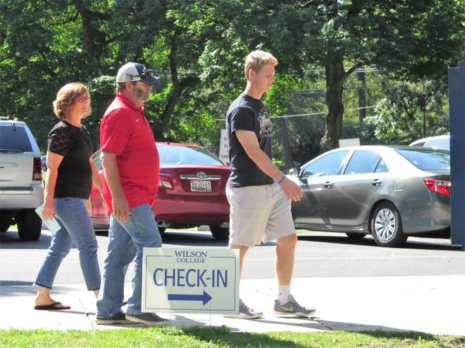A student and his parents walk toward the check-in area at Wilson College on Thursday. New and returning students arrived at the Chambersburg campus this week ahead of the first day of classes Monday.