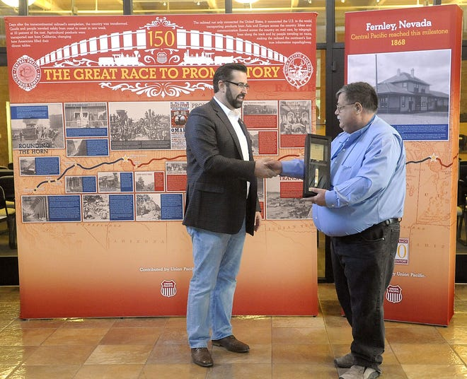 Union Pacific Public Affairs Director Nathan Anderson presents Mayor Roy Edgington with a commemorative golden spike.