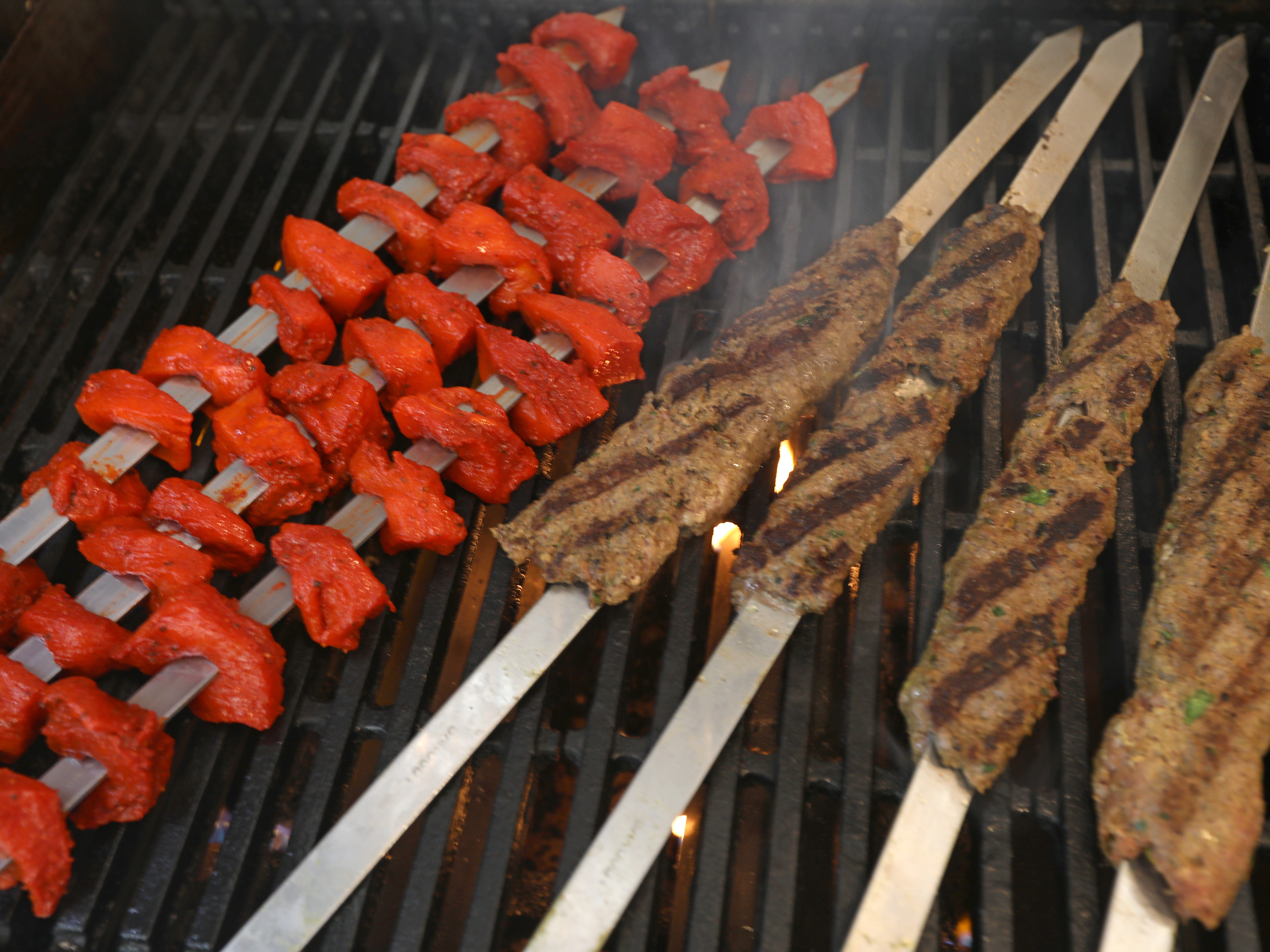 Skewers of tandoori chicken and beef pack the grill.