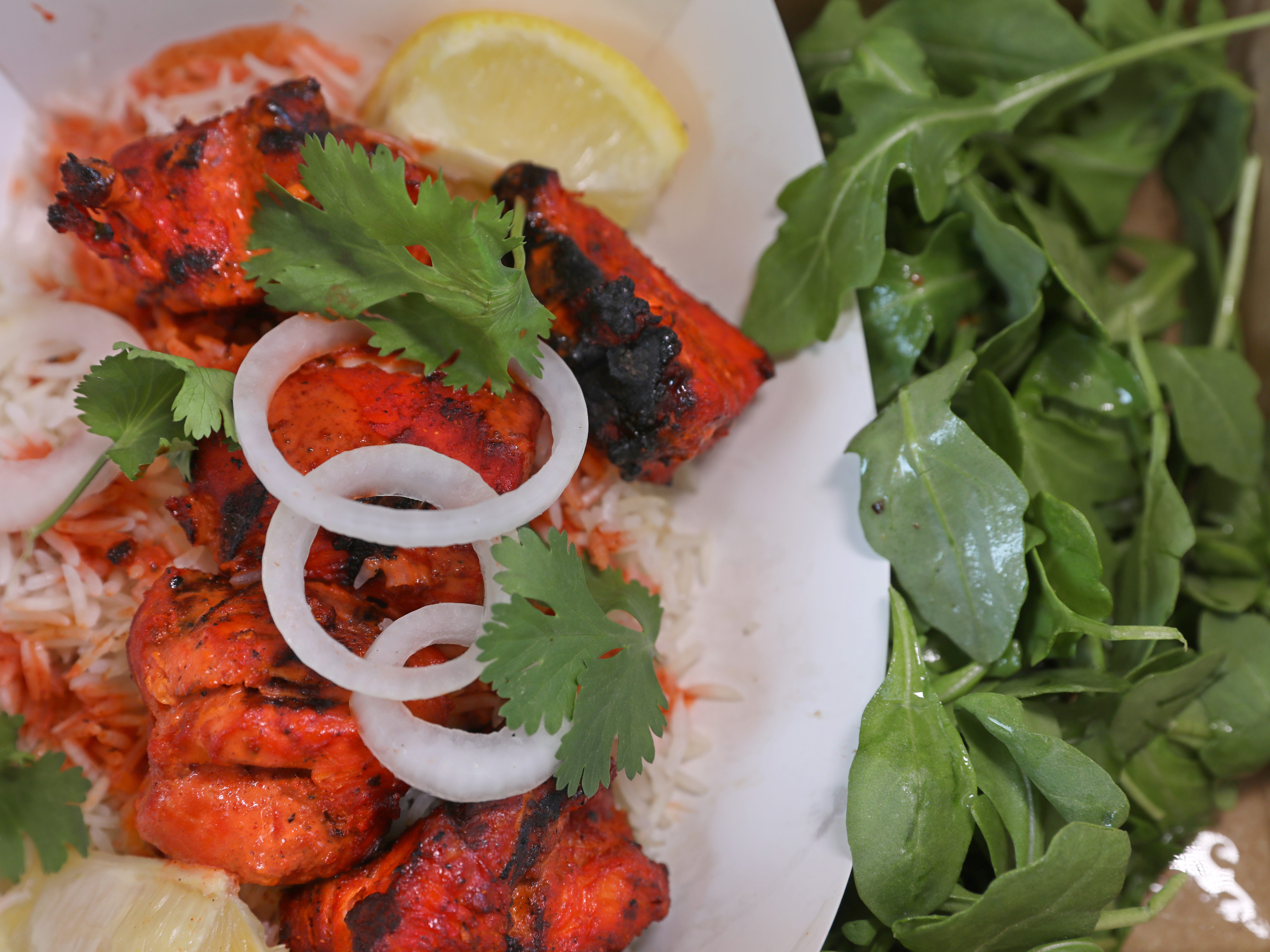 Tandoori chicken served with rice and a salad on the Taste the ROC food truck.