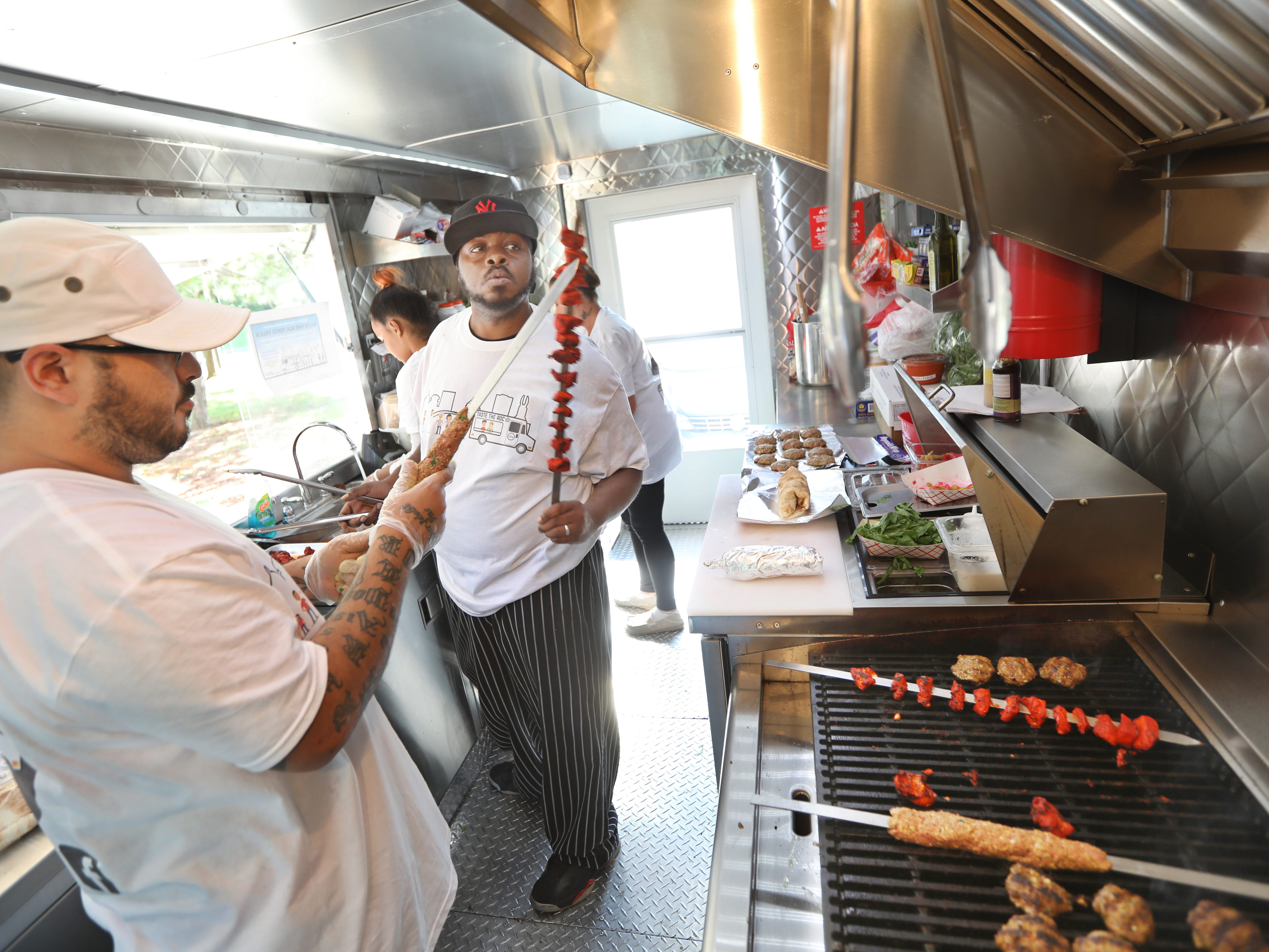Wilmer King, center, checks a skewer of Tandoori chicken as he takes it off the grill while Raul Ortiz, left, readies a skewer of beef for grilling inside the new Taste the ROC food truck.