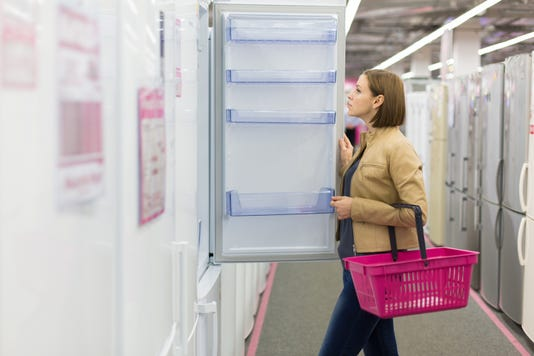 Woman Buys A Refrigerator In The Store