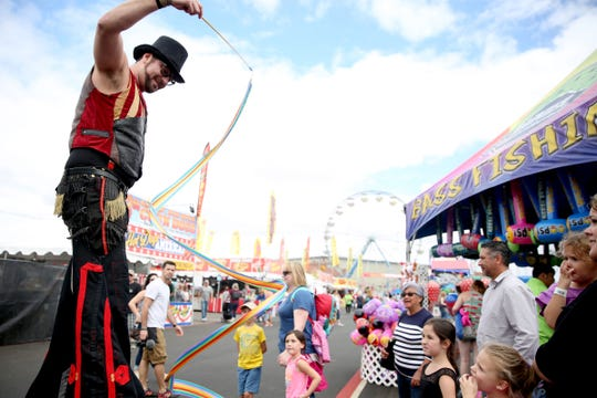Jon Dutch, with he Rose City Circus, performs on stilts for people on the opening day of the Oregon State Fair in Salem on Friday, Aug. 24, 2018.