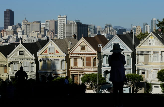 "A woman looks toward the ""Painted Ladies,"" a row of historical Victorian homes, with the San Francisco skyline at rear at Alamo Square Park in San Francisco."
