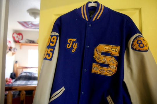 Ty Hart's Stayton High School letterman jacket hangs on his bedroom door at his parents' home in Aumsville on Friday, Aug. 24, 2018. Lance Cpl. Ty Hart was one of 12 Marines who died in 2016 when two military helicopters collided during a training exercise in Hawaii. His family started a scholarship in his name so children and their families can afford to pay for sports equipment or training.