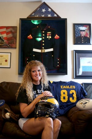 Trina Hart, the mother of Ty Hart, sits for a photo with some of his sports gear at her home in Aumsville on Friday, Aug. 24, 2018. Lance Cpl. Ty Hart was one of 12 Marines who died in 2016 when two military helicopters collided during a training exercise in Hawaii. His family started a scholarship in his name so children and their families can afford to pay for sports equipment or training.