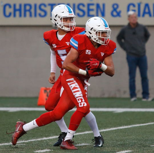 North Salinas's quarterback Jake Sotelo hands off to Matt Morales against North Monterey County's during football at Rabobank Stadium in Salinas on Thursday August 23, 2018.