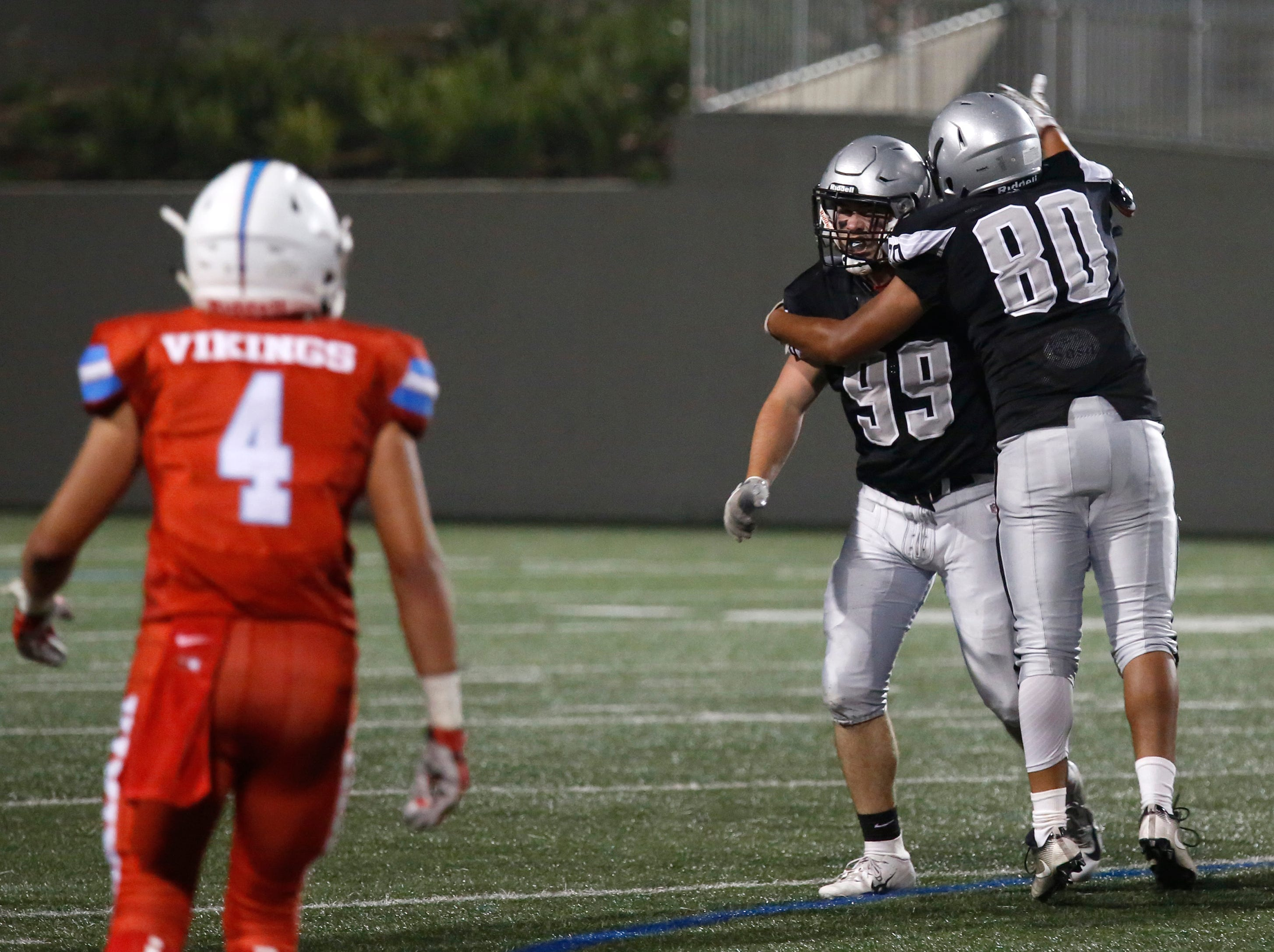 North Monterey County's Konan VanLear, left, is greeted by teammate Felix Perez reacts after his sacking of North Salinas's quarterback during football at Rabobank Stadium in Salinas on Thursday August 23, 2018.