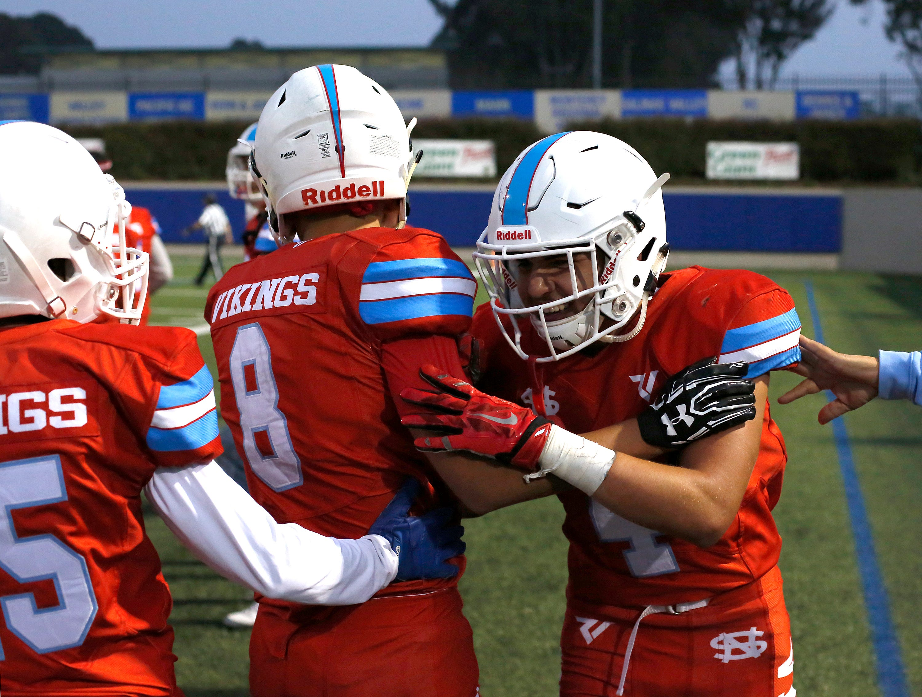 North Salinas's Matt Morales, right, is greeted by team mates after running in a touchdown against North Monterey County during football at Rabobank Stadium in Salinas on Thursday August 23, 2018.