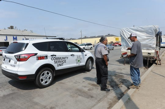 A community service officer speaks with David Hullfish about the oversized vehicle ban, which goes into effect Monday.
