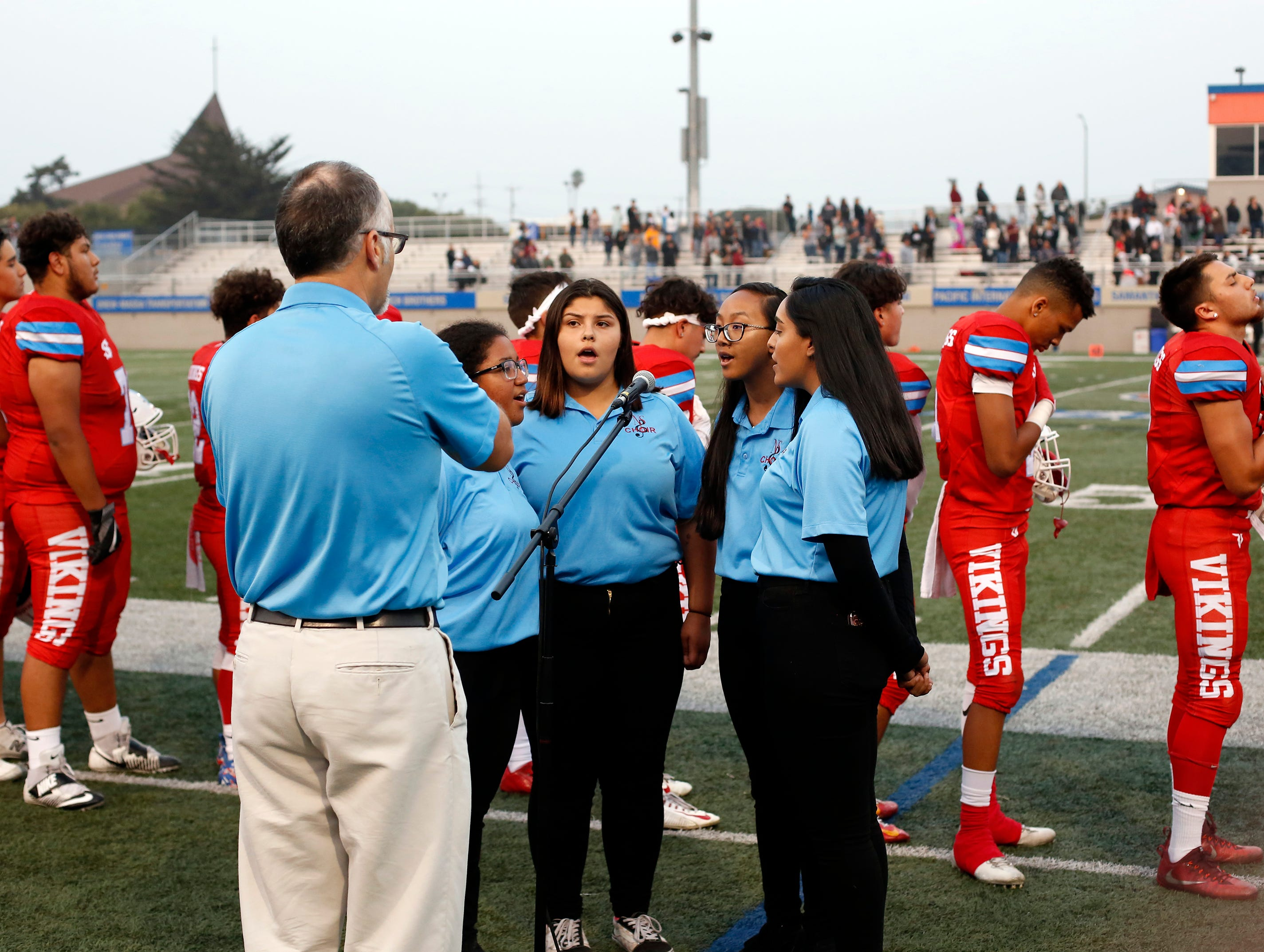 North Salinas players listen to the National Anthem sung by choir members before taking the field against North Monterey County during football at Rabobank Stadium in Salinas on Thursday August 23, 2018.