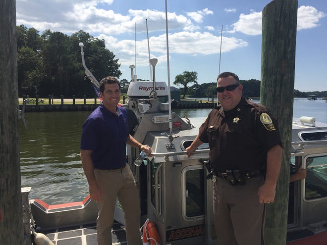 Rep. Scott Taylor steps aboard the Accomack County Sheriff's Office boat with Capt. Todd Wessells of the Sheriff's Office at the wharf in Onancock, VIrginia on Friday, Aug. 24, 2018. Taylor and Del. Rob Bloxom traveled aboard the boat to Tangier for an announcement.