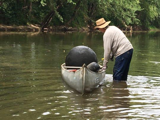 Stream Team 3 member Dave Farris prepares to float the heavy sphere downstream in his aluminum canoe.