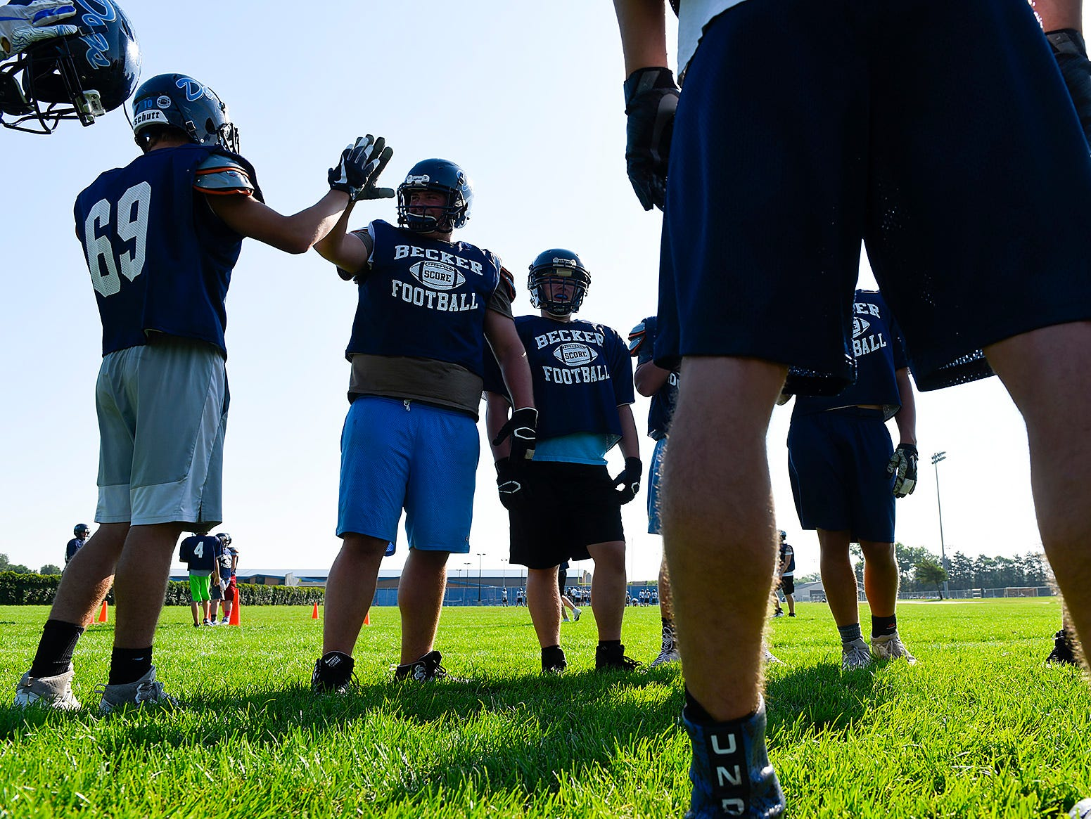 Becker celebrate a play in the huddle Wednesday, Aug. 22, at the Becker High School.