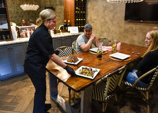 Sous chef Kayla Strom presents sample meals to Jeff Buresh and his fiancé, Alex Bourdeaux, as they plan their wedding Friday, Aug. 24, in the tasting room at Custom Catering by Short Stop in St. Cloud.