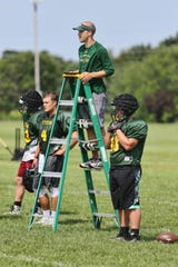 Head Coach Philip Klaphake utilizes the iPad while getting a different perspective on 11-on-11 drills during practice Wednesday, Aug. 15, at Sauk Rapids-Rice High School.