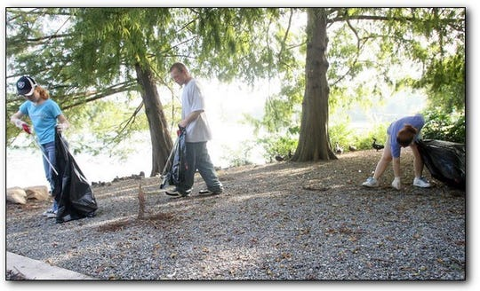 Volunteers collect trash around Lake Ella at the annual Shore Cleanup.