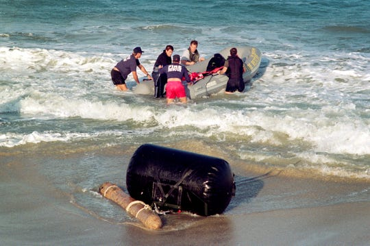 """December 3, 1996 - Navy and Indian River County Fire Rescue personnel drag what was thought to be a 40-50 year-old rocket containing a live warhead out of the ocean near the Sandpointe area which was blown up at sea. The rocket, which was identified by Navy officers as a """"Tiny Tim"""" rocket from either WWII or the Korean conflict, was dug out of 3 feet of sand, attached to a floating device and taken about three-quarters of a mile offshore where it was detonated in 20-30 feet of water."""