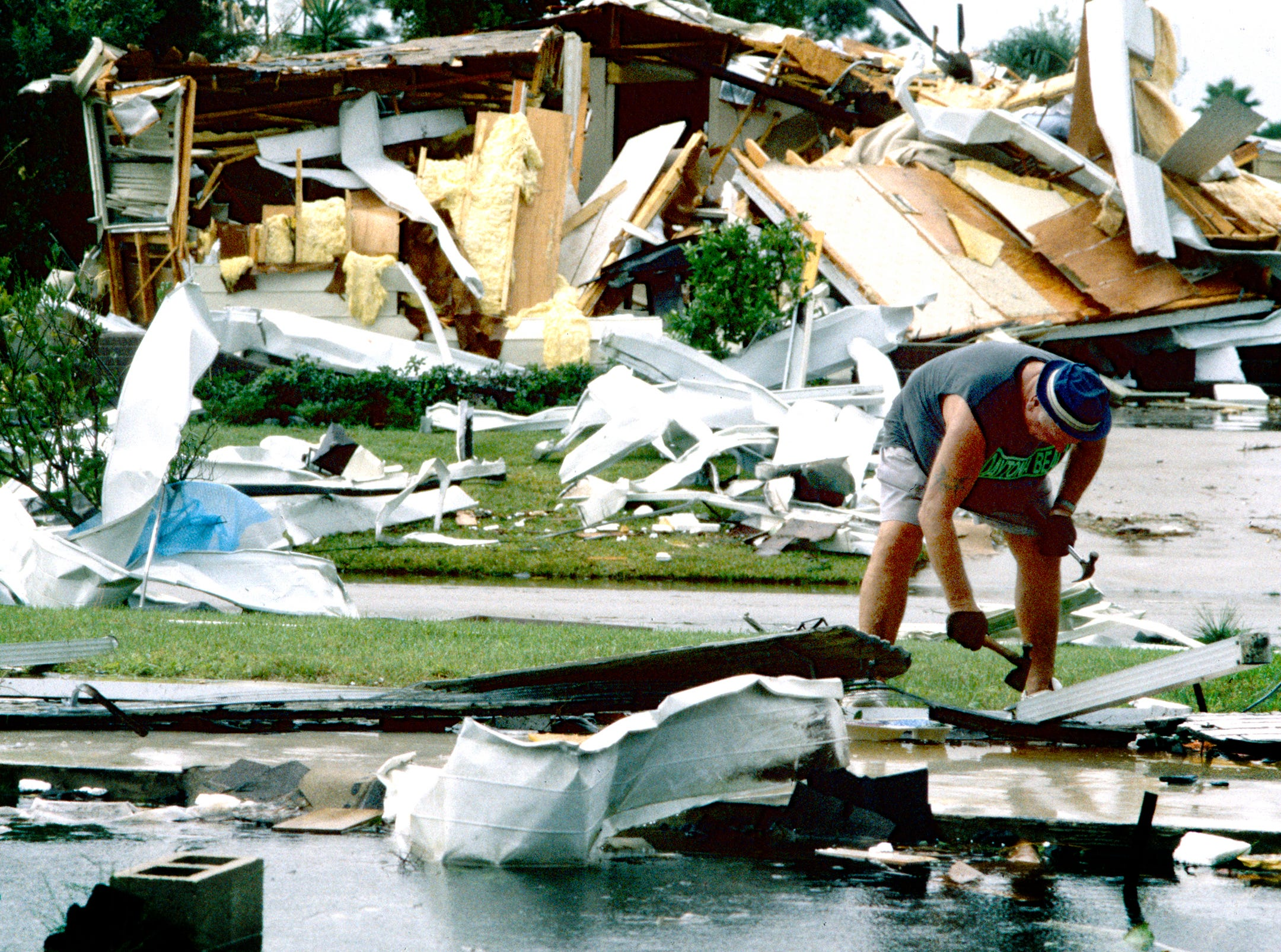November 16, 1994 - Robert Sacco works where a neighbor's home in Barefoot Bay used to be on the corner of Lantania Drive and East Periwinkle Circle. The tornado picked up the home and blew it across the street, behind were Sacco is standing, into the front yard of a neighbor's home.