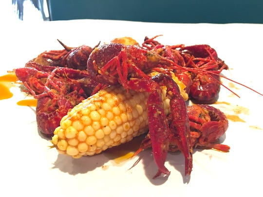 A 1-pound order of crawfish with additional corn and potatoes is seen on a table at Captain's Cajun Boil in Oxnard.