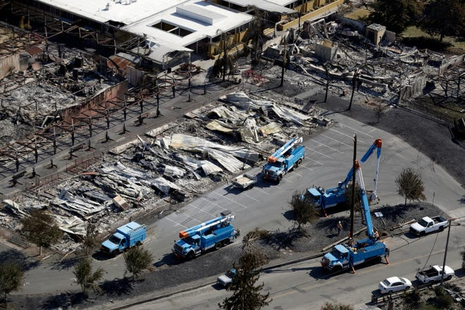 In this Oct. 14, 2017, file photo, PG&E crews work on restoring power lines in a fire ravaged neighborhood in an aerial view in the aftermath of a wildfire in Santa Rosa. California utilities could sell bonds and pass on the cost to their customers to help cover debt incurred when their equipment starts wildfires under a new legislative proposal.