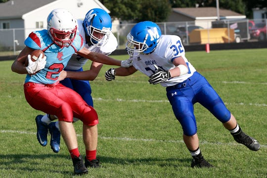 Wausau Newman's Elliot Samuels tries to break away from a pair of Chippewa Falls McDonell defenders after catching a pass against the Macks on Aug. 23. The Cardinals are in their second year as a 8-player program and are coming off an undefeated season.