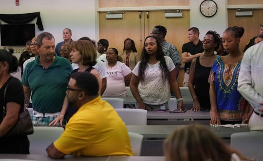 Family and friends of victims of cold cases stand in recognition at a press conference announcing a new initiative with playing cards, to be sold in the Department of Correction Commissaries throughout Delaware featuring victims images and information in hopes of getting leads to solve the crime.