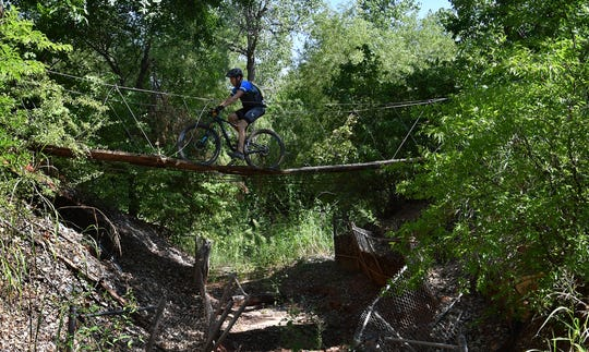 A rider makes his way across a suspension bridge while competing in the Hotter'N Hell Hundred Wee-Chi-Tah trail mountain bike races Friday morning.