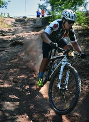 A competitor in the Hotter'N Hell Hundred Wee-Chi-Tah trail mountain bike races slides down a rocky drop Friday morning as racing got underway.