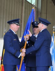 Presiding official for an assumption of command ceremony, Major General Patrick Doherty, commander of the Nineteenth Air Force, left, passes the guidon Friday to Colonel Russel Driggers, new commander of the 80th Flying Training Wing at Sheppard Air Force Base.